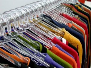 T-shirts hanging on hangers on a wrack