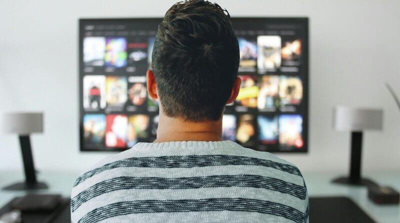 Person sitting in front of television screen