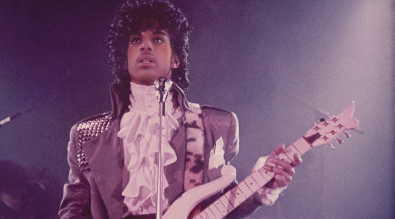 The singer Prince playing guitar at a concert