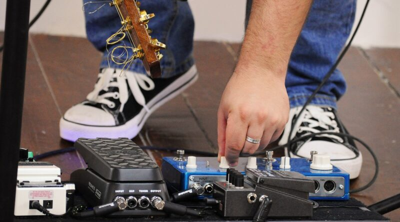 Guitar pedals with man changing settings