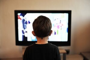 child standing in front of a TV screen