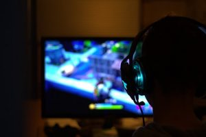a person with gaming headphones on playing a video game in front of a tv screen