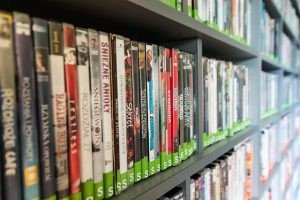 Movies propped up on shelves at a store
