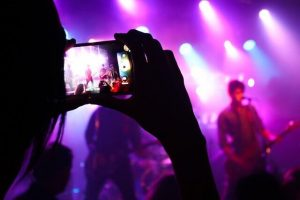 Person recording a band on their phone at a concert