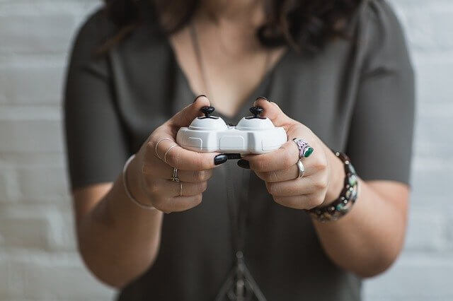 woman holding a white wireless video game controller