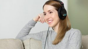 woman sitting on couch wearing headphones